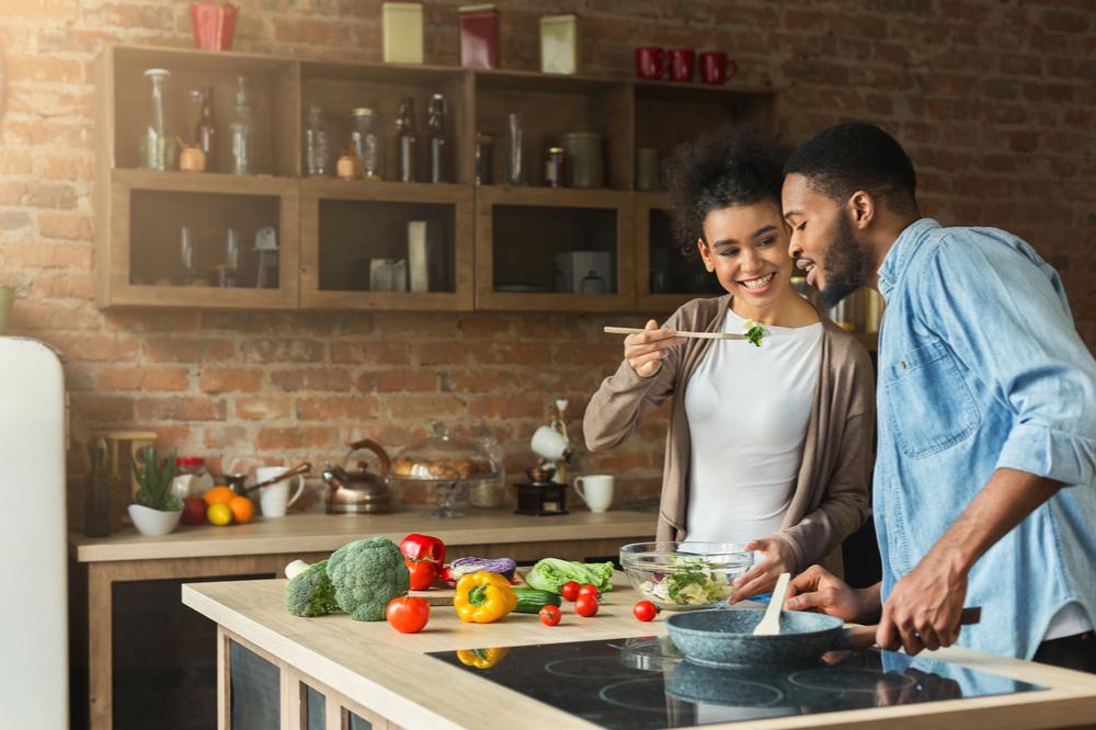 casal cozinhando legumes e verduras