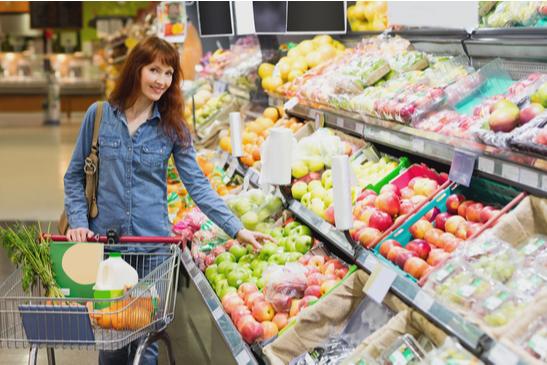 mulher adulta fazendo compra de legumes no supermercado